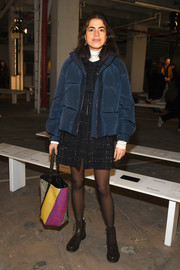 Leandra Medine teamed a navy puffer jacket with a tweed mini dress for the Proenza Schouler fashion show.