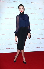 Miranda looked sleek and sophisticated in this sheer, loose blouse with a high turtleneck collar.