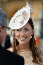 Kate Middleton attended a Buckingham Palace garden party wearing a beige and white fascinator by Jane Taylor.