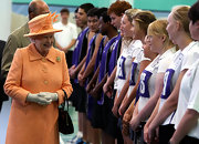 Queen Elizabeth isn't afraid of bright colors.  This tangerine textured coat and matching hat with elegant white gloves makes this look truly regal.