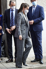 Queen Letizia of Spain kept it appropriately business-chic in a gray plaid pantsuit by Hugo Boss while attending a meeting at the Royal Academy of Engineering.