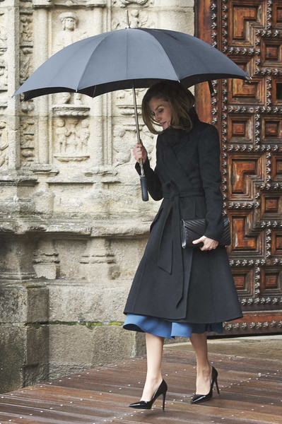 Queen Letizia of Spain kept the rain out with a black stick umbrella.