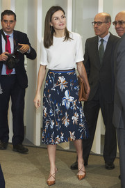 Queen Letizia of Spain paired a white Adolfo Dominguez silk blouse with a blue floral skirt for a meeting with FAD Foundation.