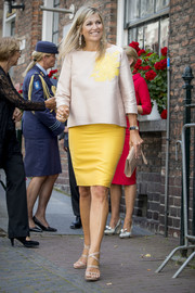 Queen Maxima paired her blouse with a canary-yellow pencil skirt.