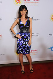 Perrey Reeves showed off her svelte figure in a dramatic black and blue mixed print cocktail dress for Charlize Theron's benefit.