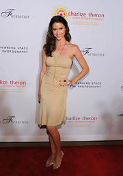 Shannon Elizabeth dazzled on the red carpet in a draped one-shoulder dress and metallic gold strappy sandals.