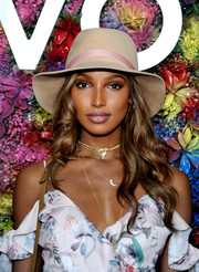 Jasmine Tookes wore a chic beige sun hat with a pink band to the Revolve Desert House party during Coachella.