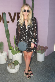 Ashley Benson completed her ensemble with a circular gray leather bag by Donatienne.