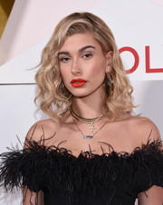 Hailey Baldwin complemented her off-the-shoulder dress with layers of necklaces when she attended the #REVOLVEawards.