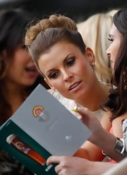 Coleen Rooney wore her hair up in a loose oversize bun while watching the races at Aintree.