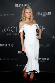 Paris Hilton looked characteristically flirty in a white lace dress with ruffle detailing at the Rachel Zoe presentation.
