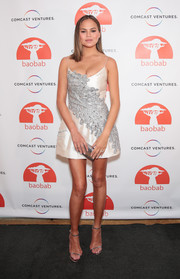 Chrissy Teigen paired her dress with silver ankle-strap sandals by Jimmy Choo.