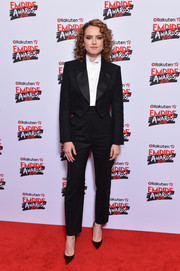 Daisy Ridley styled her suit with dark red velvet pumps by Christian Louboutin.
