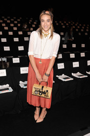 Mia Moretti looked conservative yet cute in a white blouse and a pleated coral skirt at the Rebecca Minkoff fashion show.