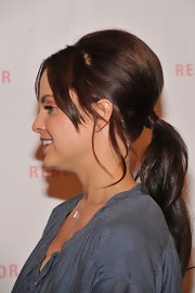 Mena sported a teased volume ponytail with loose center-parted pieces framing her face. She covered the rubberband by wrapping her hair around the ponytail for a polished finish.