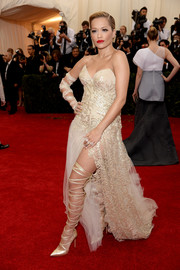Rita Ora struck a fierce pose on the Met Gala red carpet wearing an embellished cream strapless gown by Donna Karan Atelier.
