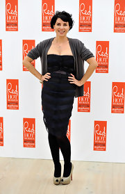 Sadie wears an edgy strapless dress with black bands and sheer inserts under a casual cardigan.