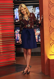 Kelly Ripa looked ultra-feminine in a chocolate floral print blouse and a blue flared skirt.