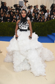 Janelle Monae floated into the Met Gala on a white cloud of tulle and lace! She added a contrasting belt and feather neckpiece in keeping with her signature black-and-white style.