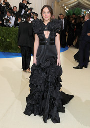 Dakota Johnson cut a super-sophisticated figure in a sculptural black cutout gown by Gucci at the 2017 Met Gala.