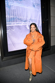 Rihanna layered an orange trenchcoat over a matching turtleneck dress for the launch of Fenty at Bergdorf Goodman.