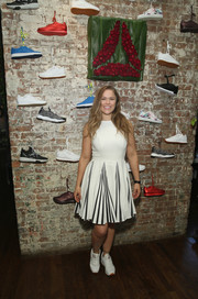 Ronda Rousey gave off cheerleader vibes in a sleeveless white dress with a pleated, striped skirt during the launch of her #PerfectNever campaign.
