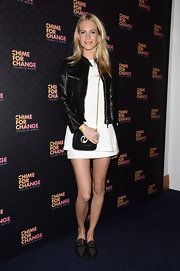 Poppy Delevingne chose a classic black leather jacket to pair over her white mini for a cool mix of styles.