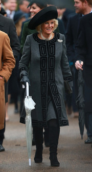 Camilla Parker Bowles paired her coat with black suede knee-high boots.