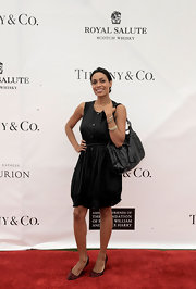 At the Foundation Polo Challenge, Rosario Dawson teamed her cotton button down frock with a glossy black woven purse with a tassel detail.