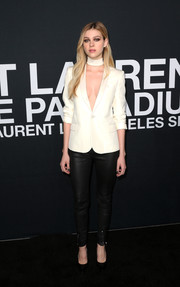 Nicola Peltz flashed some cleavage in a white blazer worn sans shirt at the Saint Laurent fashion show.