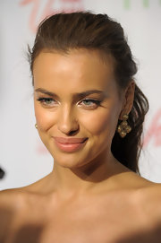 Irina Shayk accented her golden cluster earrings by pulling her long brunette curls back in a sleek ponytail.