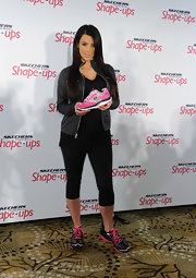 Kim Kardashian announced her partnership with Skechers wearing a pair of the line's Shape-ups in black and pink. The reality star posed while holding a similar shoe in pink and gray.