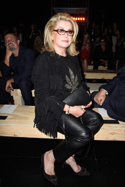 Catherine Deneuve amped up the edgy vibe with a pair of black leather pants.