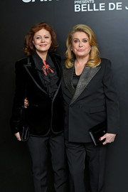 Catherine Deneuve teamed a black leather clutch with a pantsuit for the 'Belle de Jour' 50th anniversary screening.