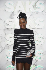 Lupita Nyong'o accessorized with a snow leopard crystal clutch by Judith Leiber at the Saks celebration.