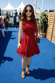 Salma Hayek visited the American Pavilion in Cannes wearing a lovely red fit-and-flare dress by Alexander McQueen.