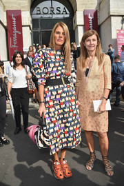 Anna dello Russo playfully teamed orange Reebok crosstrainers with her multicolored dress.