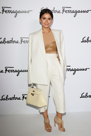 Miroslava Duma looked quite the cosmopolitan girl in a white Ferragamo pinstripe pantsuit worn with a leather bra top during the Ferragamo fashion show.