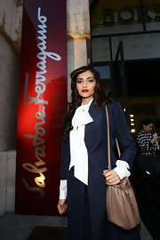 Sonam Kapoor went to the Ferragamo fashion show carrying a stylish leather shoulder bag with a drawstring enclosure.