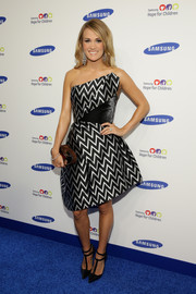Carrie Underwood polished off her look with a mirrored oval clutch.