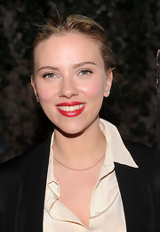 Scarlett Johansson attended a fundraiser wearing glossy red lipstick with a subtle pearlescent finish.