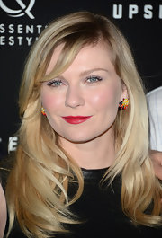 Kirsten Dunst opted for vibrant red lips to add a splash of color to her fair skin.