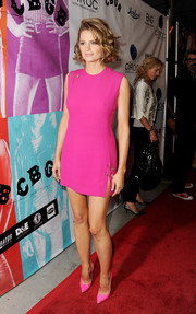 Stana Katic brought a bright pop of color to the 'CBGB' premiere in a safety pin-embellished hot-pink mini dress by Versace.
