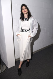 Coco Rocha arrived for New York Fashion Week wearing a loose white cardigan.