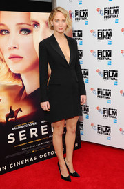 Jennifer Lawrence struck the perfect balance between classy and sexy in a cleavage-revealing coat dress by Christian Dior during the 'Serena' premiere.