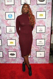Venus Williams sheathed her svelte figure in a body-con turtleneck sweater dress from sister Serena's Signature Statement collection.