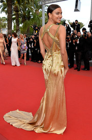 Irina Shayk put plenty of skin and curves on display in a backless gold Versace gown during the 'Sicario' premiere in Cannes.