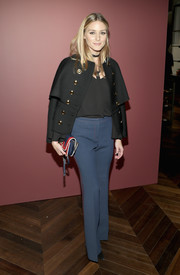 Olivia Palermo paired a black military jacket with a pair of side-striped blue pants for the 'Tale of Thomas Burberry' celebration.