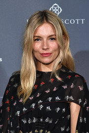 Sienna Miller wore her hair in a center-parted style with barely-there waves at the International Medical Corps summer cocktail event.