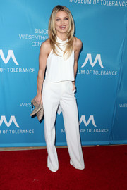 AnnaLynne McCord styled her white separates with a gold foldover clutch.